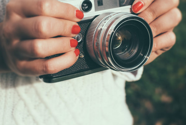 oung woman with a retro camera