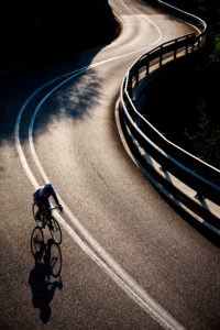 One male cyclist riding along a paved mountain road on a road bike. Back-light effect, vertical frame