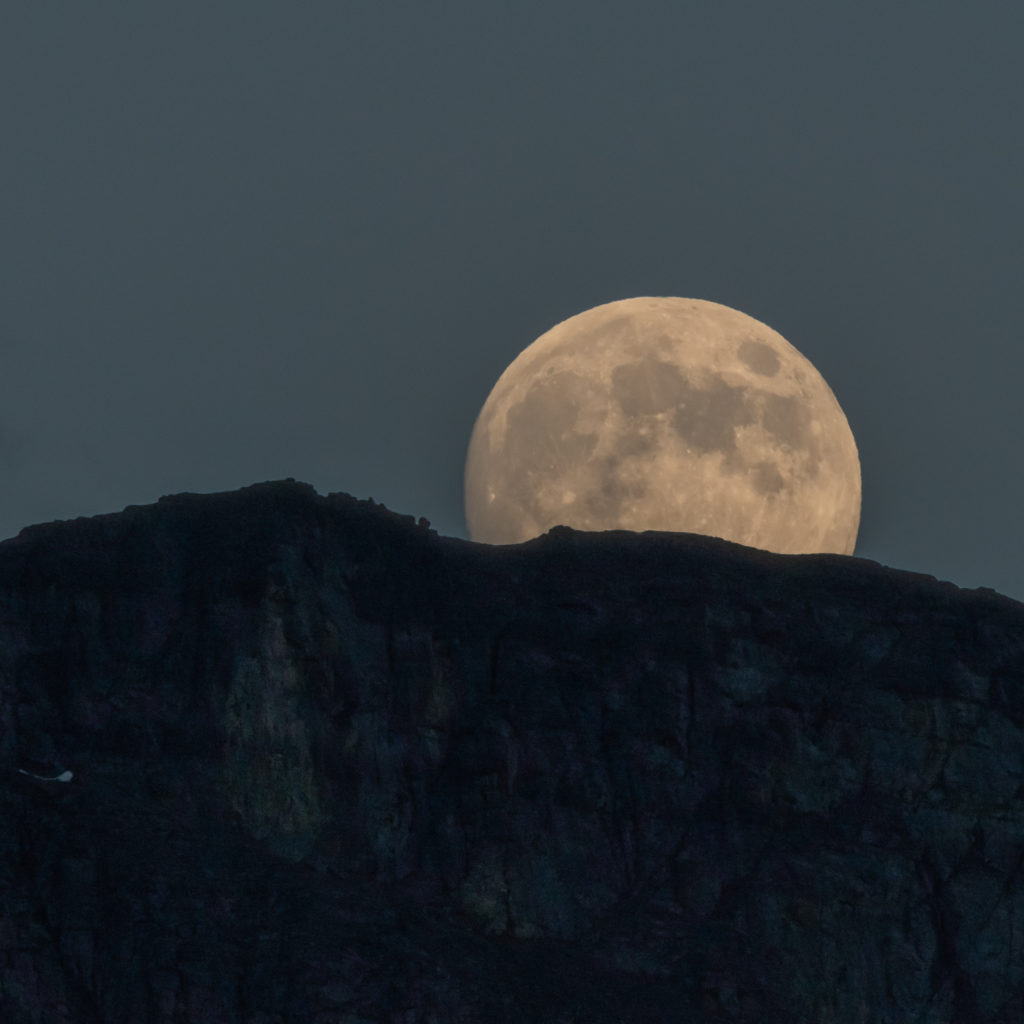 Full Moon Emerges Behind Mountain