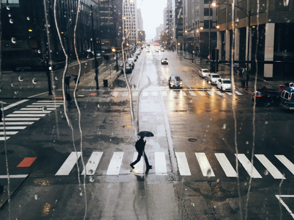 Man with umbrella crossing on the street
